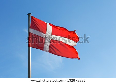 Flag of Denmark against blue sky - stock photo