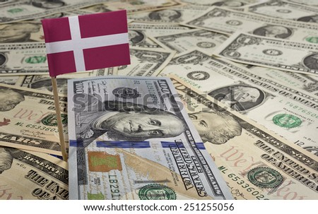 Flag of Denmark sticking in a variety of american banknotes.(series) - stock photo