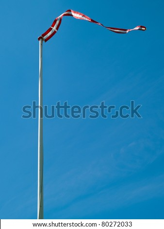 Flag of Denmark up high with clear blue sky background vertical image - stock photo