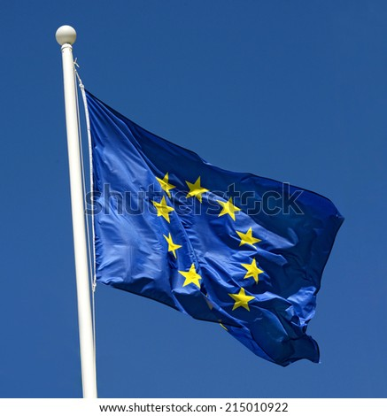 Flag of European Union fluttering in the wind, against a clear blue sky, concept of freedom and unity