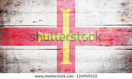 Flag of Guernsey painted on grungy wood plank background - stock photo