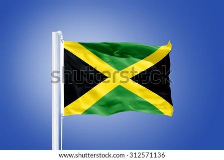 Flag of Jamaica flying against a blue sky. - stock photo