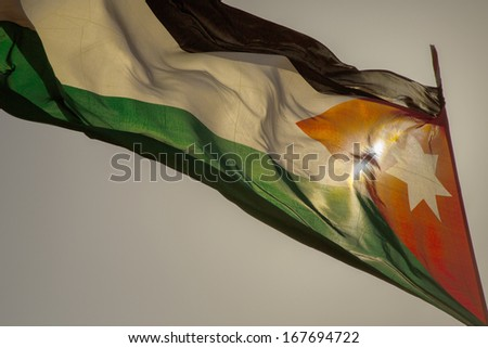 Flag of Jordan back-light with sun form of a silhouette with a lot of empty space  - stock photo