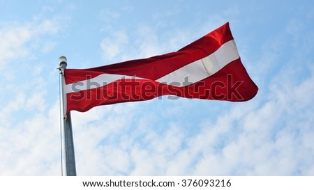 Flag of Latvia on a flagpole against blue sky with clouds - stock photo