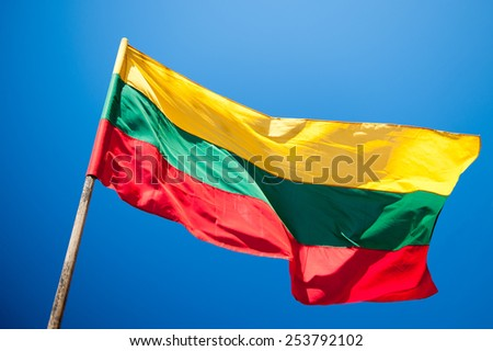 Flag of Lithuania over blue sky background - stock photo
