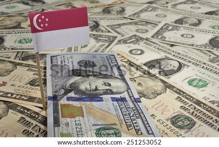 Flag of Singapore sticking in a variety of american banknotes.(series) - stock photo