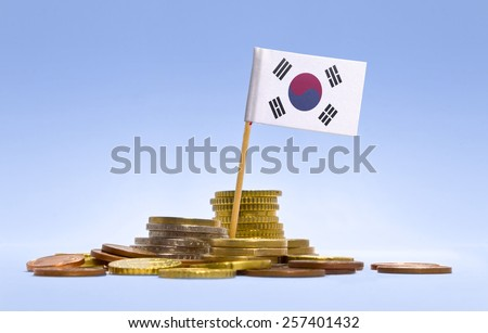 Flag of South Korea in a mixed stack of european coins and a blue background.(series) - stock photo