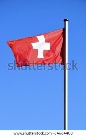 Flag of switzerland waving in front of a blue sky - stock photo