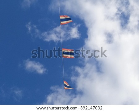 Flag of Thailand with blue sky background.