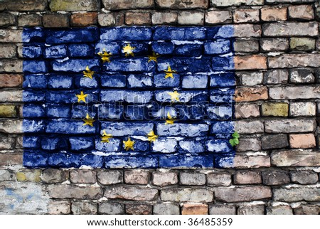 Flag of the European Union painted on an old brick wall with small ivy plant growing out of a crack. - stock photo