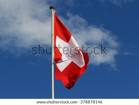 Flag of the Federal State of Switzerland flapping in the wind against blue skies and white clouds - stock photo