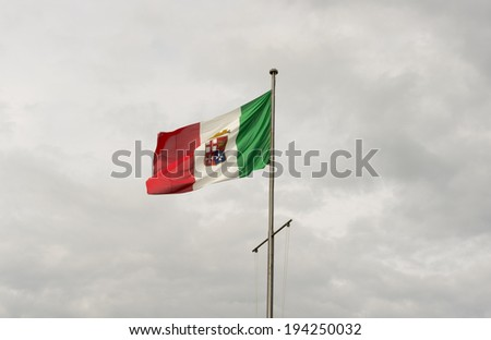 Flag of the Italian Navy flies in the sky over Cagliari - stock photo