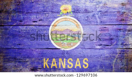 Flag of the state of Kansas painted on grungy wooden background - stock photo