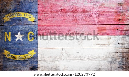 Flag of the state of North Carolina painted on grungy wooden background - stock photo