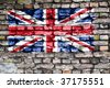 Flag of the United Kingdom on an old brick wall with small ivy plant growing out of a crack. - stock photo