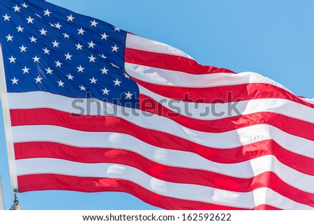 Flag of the United States on the blue sky - stock photo