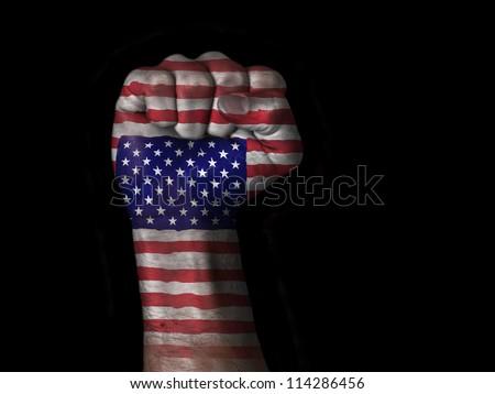 Flag of the United States painted on raised fist - stock photo