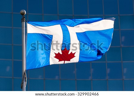 Flag of Toronto city. The flag displays twin towers of the Toronto City Hall on a blue background, with the red maple leaf at its base representing the Council Chamber.  - stock photo