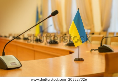 Flag of Ukraine on the negotiating table - stock photo