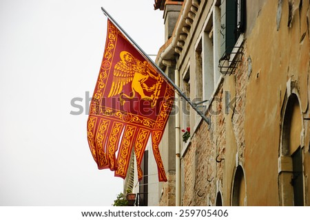 Flag of Venice with winged lion and old Venetian building on background. Cloudy winter day. - stock photo
