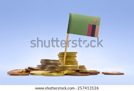 Flag of Zambia in a mixed stack of european coins and a blue background.(series) - stock photo