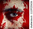 flag painted on face of a national team supporter, close up of a male eye. - stock photo