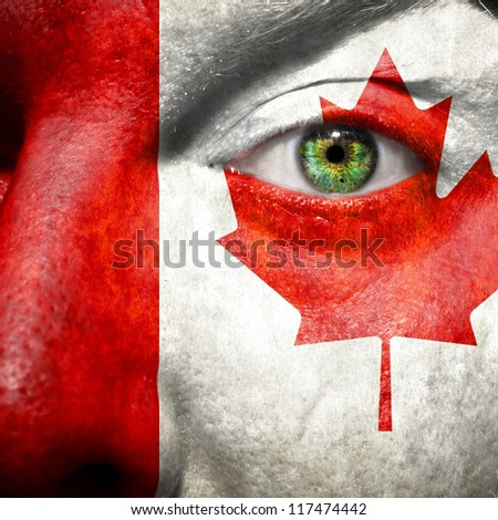 Flag painted on face with green eye to show Canada support