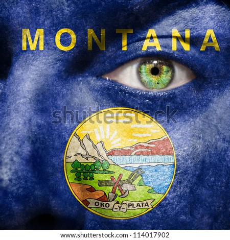 Flag painted on face with green eye to show Montana support - stock photo