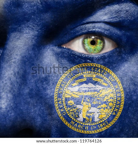Flag painted on face with green eye to show Nebraska support - stock photo