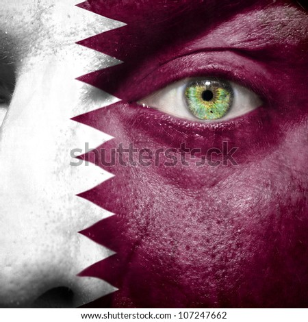 Flag painted on face with green eye to show Qatar support - stock photo