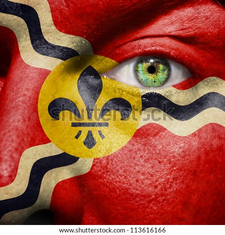 Flag painted on face with green eye to show St Louis support - stock photo