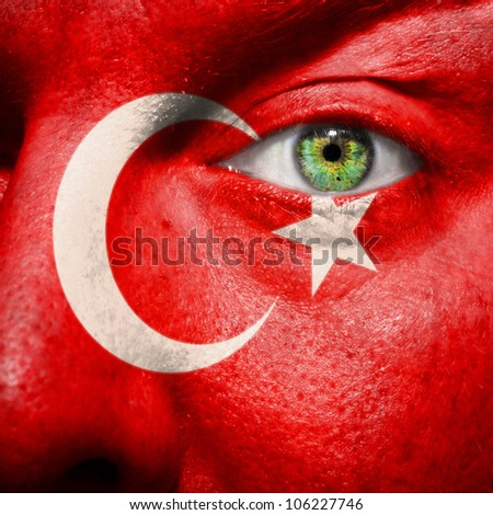 Flag painted on face with green eye to show Turkey support - stock photo