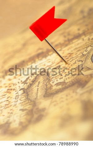 Flag red a pin on old map. Photo closeup. Selective focus - stock photo