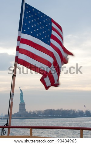 Flag whipping in the breeze in front of statue of liberty through the mist at sunset. - stock photo