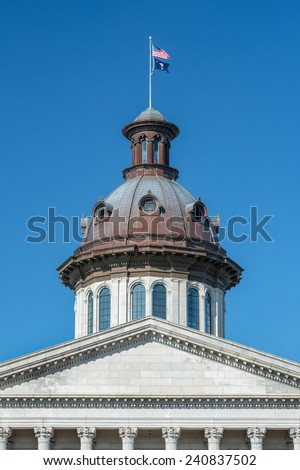 Flags fly over the dome of the South Carolina State House in Columbia, South Carolina - stock photo