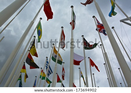 Flags of all nations of the world are flying in grey cloudy sky - stock photo