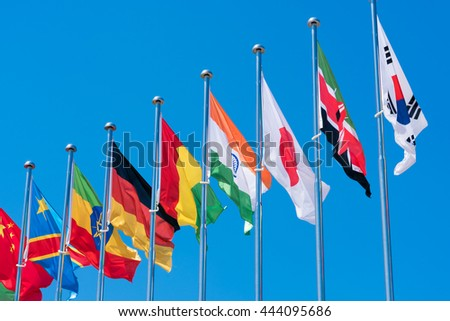 Flags of different countries on the background of the blue sky - stock photo