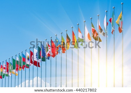 Flags of different countries on the background of the blue sky in the sunlight - stock photo