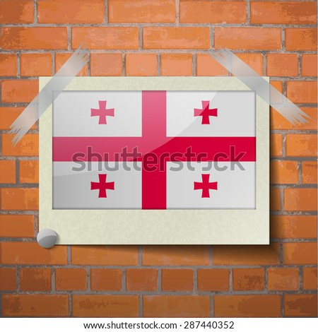 Flags of Georgia scotch taped to a red brick wall.  Rasterized version - stock photo