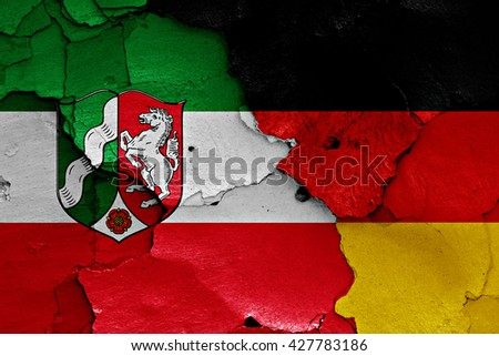 flags of North Rhine Westphalia and Germany painted on cracked wall - stock photo