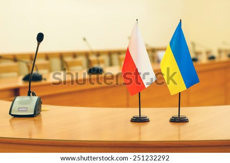 Flags of Poland and Ukraine on the negotiating table - stock photo
