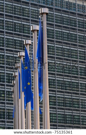 Flags of the European Union are hanging besides the headquarters of the European Commission in Brussels, Belgium. - stock photo
