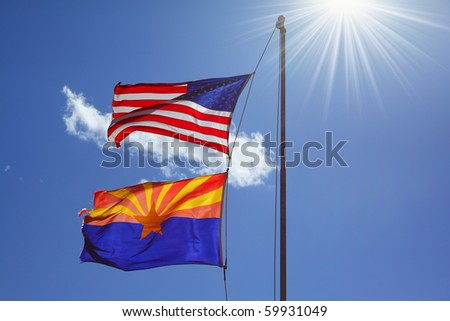 Flags of the United States and the Navajo Reservation are flying against the shining sun - stock photo
