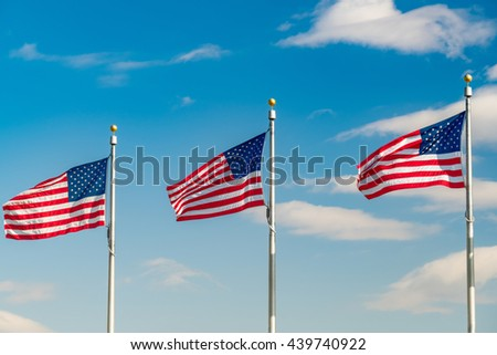 Flags of the United States waving over blue sky in Washington DC - stock photo