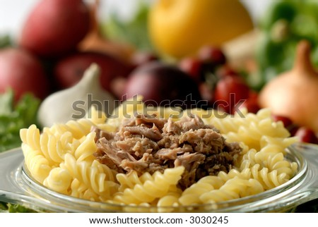 Flaked tuna on a noodle against vegetable background - stock photo
