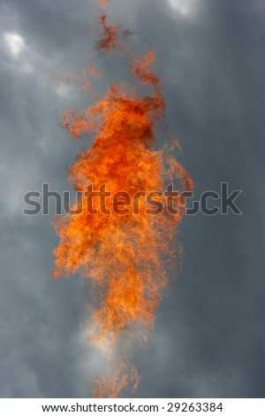 Flame against a grey sky - stock photo