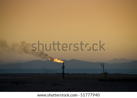 Flame from an oil pipe at sunset with mountains in the background. South Sinai, Egypt.
