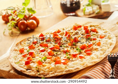 Flame grilled traditional Alsatian french pizza topped with mozzarella cheese, ham or bacon cubes, onion and fresh herbs in a rustic kitchen viewed low angle - stock photo