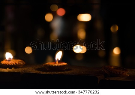 flame light on small pottery candle base. object's on wood floor in dark area with abstract defocused bokeh light background - stock photo