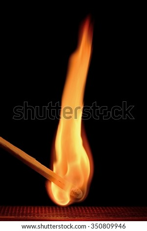 Flame of a Lit Match Against a Black Background - stock photo
